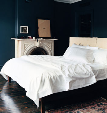 Domino Magazine. J.Crew Creative Director Jenna Lyon's bedroom. Dark black walls seem to be the new trend, but in this room it isn't paint but chalkboard paint. That would be great to paint on one wall in a child's room, then they can actually draw on the walls.