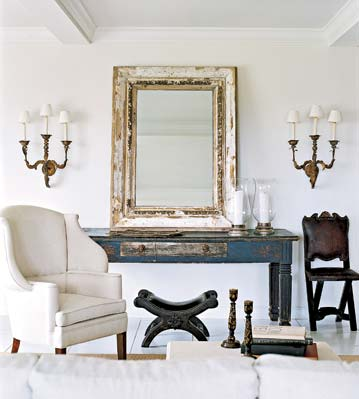 Elle Decor. Designer Darryl Carter is known for creating polished and refined rustic spaces. I love the combination of the weathered console table and mirror with the traditional wing chair and gold sconces.