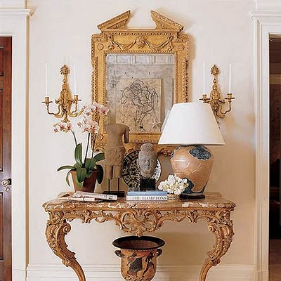 Elle Decor. The beautiful antique French table and gold gilt frame makes for a grand entrance to this home. Although there is a lot on the console table, no one item loses its unique appeal.