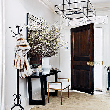 Thom Filicia. This entry has beautiful lines with the geometric chandelier and the cut-out legs of the console table. There is a repetition of the rectangles throughout the space. I love the combination of dark wood and natural tones, it gives the space a Napa Valley elegance.