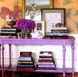 The purple console table and colorful wallpaper make a bold first impression and are a clear indication of the homeowner's more intrepid use of bold color. Many people will use stacks of books in an entry to give the space some height.