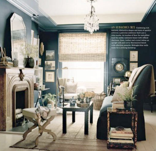 Domino Magazine. Dark walls seem to be a new trend. This room has an eclectic collection of pieces, but I love the strength of the black walls, black upright couch, and black leather nail head coffee table.
