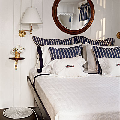Coastal Living Magazine. This room is a perfect example of how navy blue and white can brighten a space. The round mirror is reminiscent of a porthole on a ship, giving this room a more nautical feel.