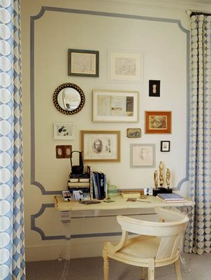 Office by designer Steve Miller. The painted blue trim and collage of photos and mirrors makes an otherwise stale white wall a beautiful backdrop to the work space.