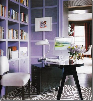 Elle Decor. This very feminine office space creates a beautiful balance between modern and traditional with the A-frame desk and paneled walls against the zebra print rug and modern desk lamp.
