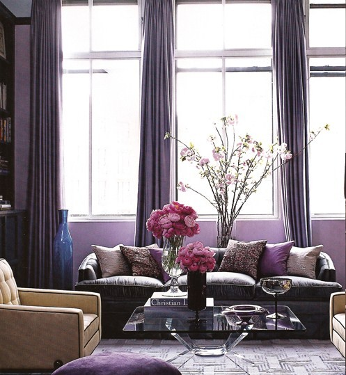 This is an ultra chic living room with the silk pillows, velvet couch and glass coffee table. The floor to ceiling silk drapes create a dramatic backdrop and emphasize the tall ceilings and oversized windows.