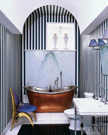 Elle Decor. The white ceilings and white tile floor balance the striped wallpaper and emphasizes the high contrast between black and white. I love the copper tub and the way that the artwork is hung off-set, drawing your eye directly to the back wall.