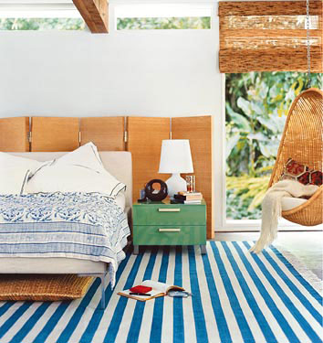 The low flung bed and bold turquoise striped rug is a modern take on beach decor. I love the hanging ratan chair!