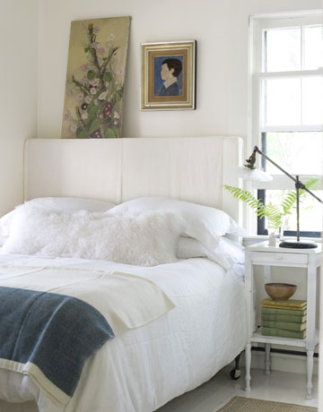 The white linen headboard adds to the casual beachy feel of the room. Despite the monochromatic scheme of the room, white exists in many different textures-linen, cotton, fur, antiqued finish, and high-sheen hardwood floors.